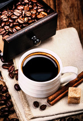 Cup of coffee with coffee beans and Coffee grinder on wooden bro