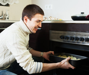 Guy roasting meat in the oven