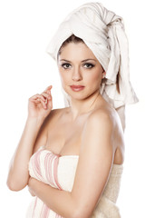 young woman with a towel on her head posing on a white