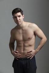 half naked man lifting weights