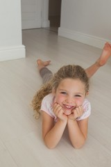 Portrait of a smiling girl lying on floor
