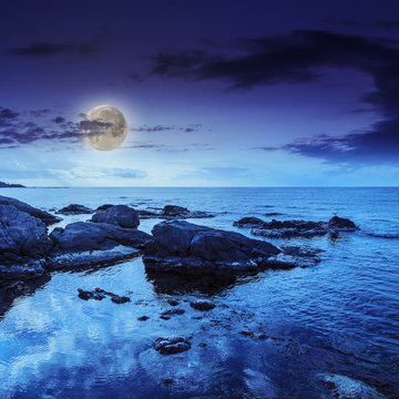 sea wave breaks about  boulders at night