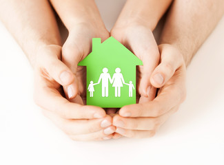 Wall Mural - hands holding green house with family