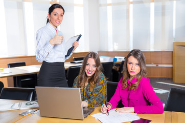 Three attractive female colleagues working in the office