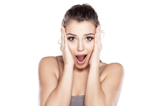 Young shocked woman on white background