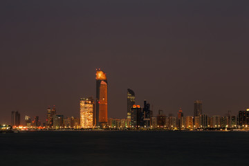 A skyline view of the Corniche Road in Abu Dhabi, UAE at dusk