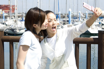 Two Japanese women in their twenties taking picture with cellular phone at port