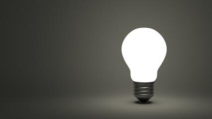 Glowing light bulb on gray