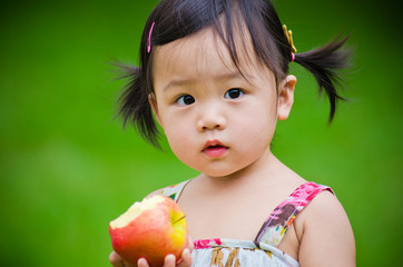 Adorable Asain little girl posing with a red apple