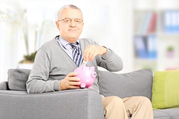 Gentleman sitting on sofa and putting money into piggybank
