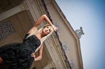 Beautiful woman in black dress posing outdoor. Sexy woman