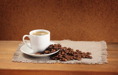 Coffee beans, cup, saucer and napkin on wooden table