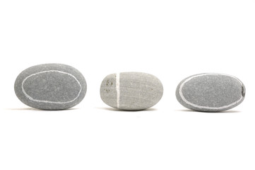 Row of assorted pebbles isolated on a white