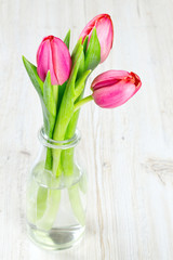 pink tulips in a glass bottle on wooden surface