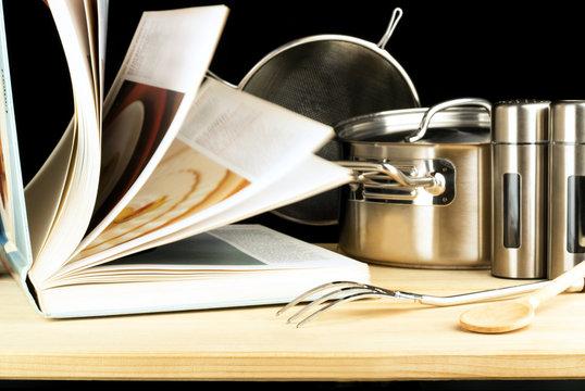 Kochbuch und Kochutensilien auf Holz