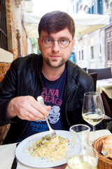 Man eating plate of pasta at cafe table