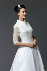 The beautiful young woman posing in a wedding dress on a grey ba