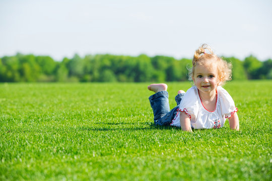 Little happy girl on a grass