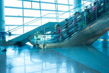 People rush on escalator motion blurred