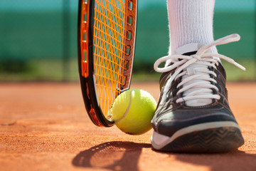 Legs of athlete near the tennis racket and ball
