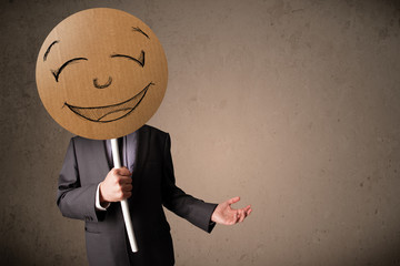 Wall Mural - Businessman holding a smiley face board