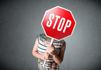 Wall Mural - Young woman holding a stop sign