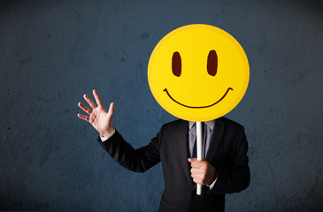 Wall Mural - Businessman holding a smiley face emoticon