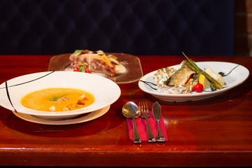 Image of baked fish with vegetables, soup and dessert on table