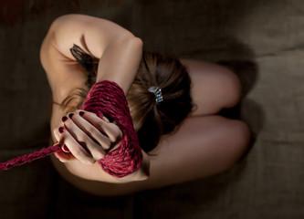 Bovenaanzicht van de handen van de vrouw gebonden met rood touw