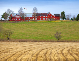 Spring rural Norwegian landscape with red house and dry field