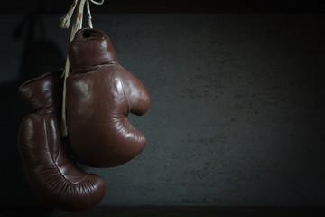 alte Boxhandschuhe, hängend vor Wand