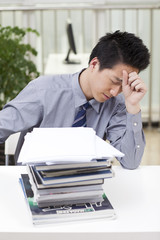 .A man looks stressed as he works at his desk.