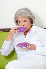 Ältere Frau trinkt Kaffee