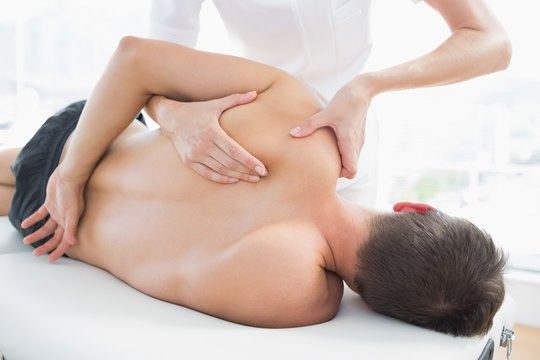 Physiotherapist giving shoulder massage to man