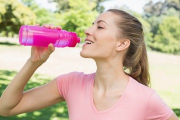 Sporty woman drinking water at park