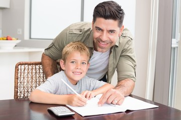 Cheerful father helping son with math homework at table