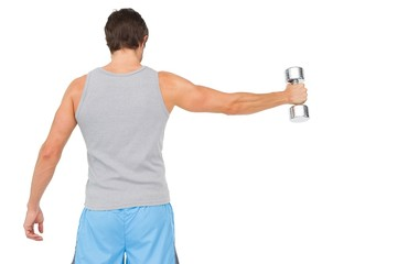 Rear view of a young man holding out dumbbell