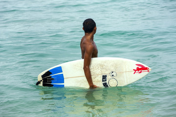 Surfer with surfboard in the ocean
