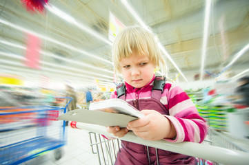 Adorable girl with serious face sit on shopping cart with brushe