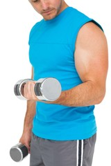 Mid section of a fit man exercising with dumbbells