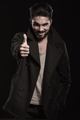 smiling fashion man with beard making the ok thumbs up
