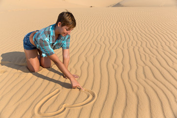 woman sitting on beach dunes and drawing Heart on the sand