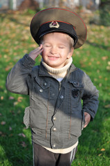 Boy salutes in military cap
