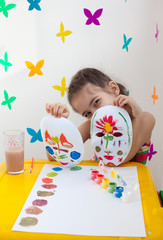 Child holding two painted masks
