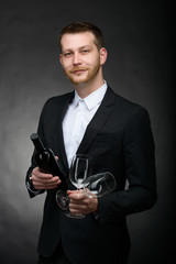 handsome romanitc man holding bottle and glasses of wine