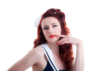 Beautiful retro pin-up girl in a sailor dress, thinking pose