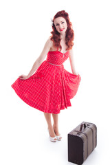 Beautiful retro pin-up girl with red dress and suitcase