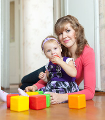 Happy mother and baby girl plays with toy blocks