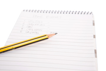 Concept image of home budget list on a notepad with pencil.
