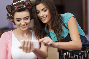 Makeup artist and female customer looking on mobile phone